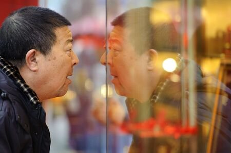 CHENGDU - FEB 7: A man stop to look in the window of a gold shop on a busy pedestrian shopping street in downtown during chinese new year on Feb 7, 2011 in Chengdu, China. Stock Photo - 9205293