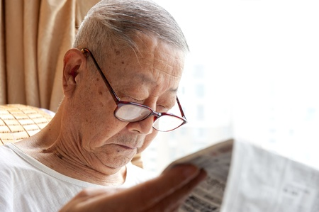 a senior man is reading newspaper photo