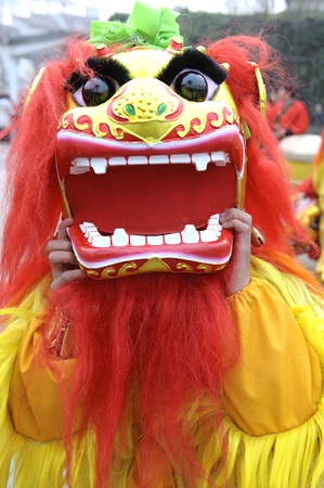 traditional custom: People playing lion dances to celebrate festivals during chinese new year,lion dances during festivals are part of the traditional custom in China.