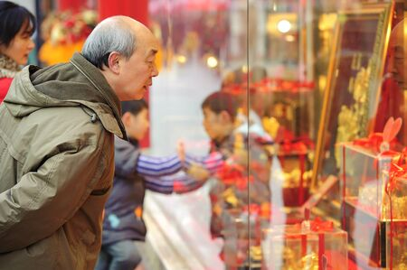 CHENGDU - FEB 7: A man stop to look in the window of a gold shop on a busy pedestrian shopping street in downtown during chinese new year on Feb 7, 2011 in Chengdu, China. Stock Photo - 9243760