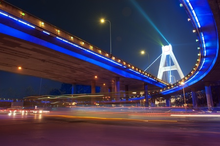High-speed vehicles blurred trails on urban roads under overpass Banque d'images