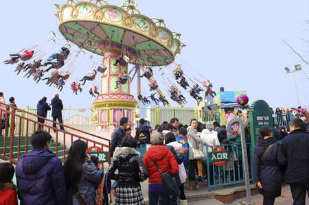 CHENGDU - FEB 3: People waiting in line to play chairoplane in the amusement park on Feb 3, 2011 in Chengdu, China. Stock Photo - 9286716