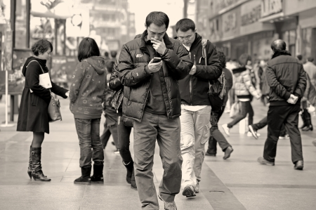 CHENGDU - FEB 7: Two men using mobile phone on a busy pedestrian shopping street in downtown during chinese new year on Feb 7, 2011 in Chengdu, China.