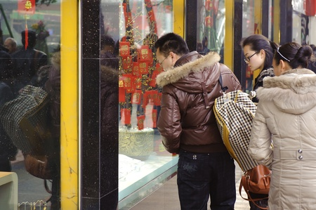 CHENGDU - FEB 7: A man and women stop to look in the window of a gold shop on a busy pedestrian shopping street in downtown during chinese new year on Feb 7, 2011 in Chengdu, China. Stock Photo - 9350525