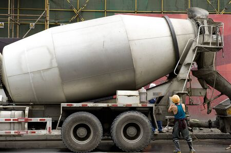 laborer: hardworking laborer and truck-concrete mixer on construction site Stock Photo
