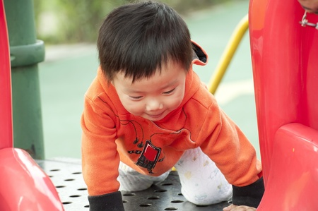baby playing on sliding board Stock Photo - 10369228
