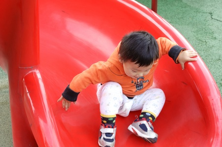 baby playing on sliding board Stock Photo - 10640324
