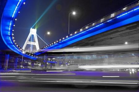 High-speed vehicles blurred trails on urban roads under overpass