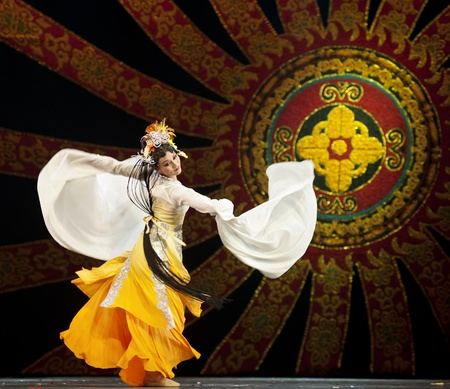 CHENGDU - OCT 17: Chinese national dancers perform folk dance on stage at JINCHENG theater on Oct 17, 2011 in Chengdu, China.