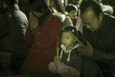 traditional custom: CHENGDU - FEB 14: Crowded people kneel down and praying to Buddha in temple during chinese new year on Feb 14, 2010 in Chengdu, China. Its part of the important traditional custom in China.