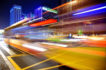 busy street: High speed and blurred bus light trails in downtown nightscape Stock Photo