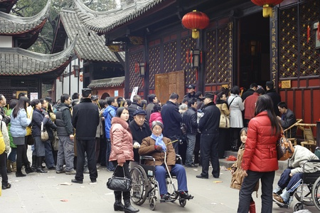 traditional custom: CHENGDU - FEB 14: crowded People waiting in line to enter a temple to pray to Buddha during chinese new year on Feb 14, 2010 in Chengdu, China. Its part of the important traditional custom in China.