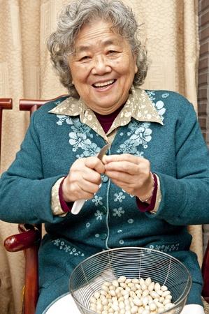 Grandmother peeling nut fruit  Stock Photo