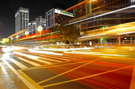 High speed and blurred bus light trails in downtown nightscape photo