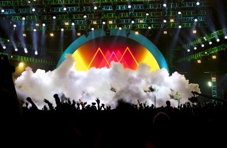 fari da palco: sagome di folla concerto di musica dal vivo di fronte a luci di scena brillanti
