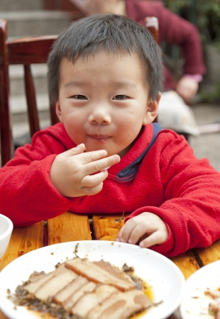 a cute baby is eating photo