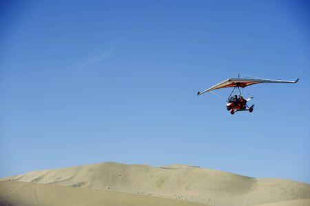 powered: powered glider flying above the desert Stock Photo