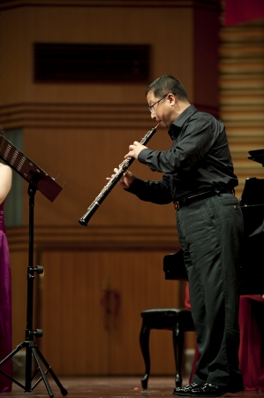 double reed: CHENGDU - JUN 20: oboist perform on wind music chamber music concert at odeum of Sichuan Conservatory of Music on Jun 20,2012 in Chengdu,China. Editorial