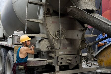 hardworking laborer and truck-concrete mixer on construction site photo