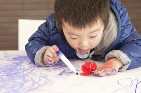 a cute baby is painting a flower photo