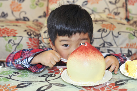 cream cake: baby boy to eat cream cake in a birthday party