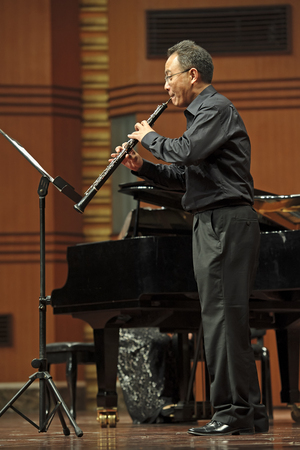 double reed: CHENGDU - JUN 20: oboist performs on wind music chamber music concert at odeum of Sichuan Conservatory of Music on Jun 20,2012 in Chengdu,China.