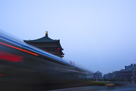 unique characteristics: high speed blurred vehicles passing in front of chinese unique bell tower in the early morning in Xian,China Editorial