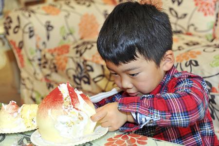 cream on cake: beb� a comer pastel de crema en una fiesta de cumplea�os Foto de archivo