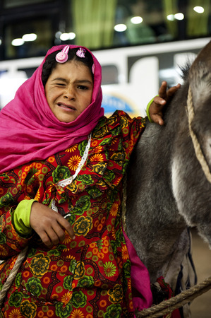 hurghada: HURGHADA - JAN 29: arab girl pulling a donkey and looking at photographer with a smile.Jan 29,2013 in Hurghada,Egypt.