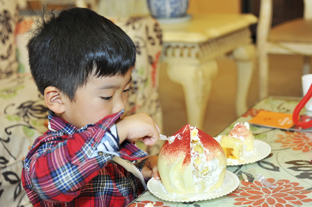 baby boy to eat cream cake in a birthday party photo