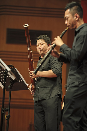 fagot: CHENGDU - JUN 20: bassoonist perform on wind music chamber music concert at odeum of Sichuan Conservatory of Music on Jun 20,2012 in Chengdu,China. Publikacyjne