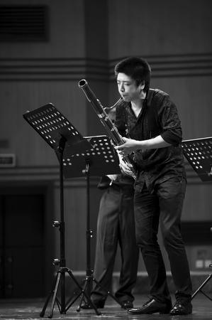 fagot: CHENGDU - 20 czerwca: fagocistą wykonać na wiatr muzyki kameralnej koncert w Odeum Sichuan Conservatory of Music w dniu cze 20,2012 w Chengdu, w Chinach.