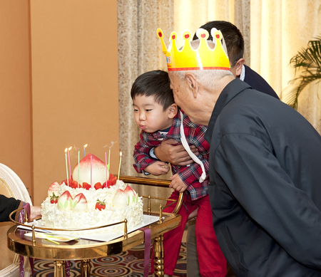 baby boy and his grandparents in the birthday party photo