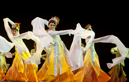hoofer: CHENGDU - OCT 17: Chinese national dancers perform folk dance on stage at JINCHENG theater on Oct 17, 2011 in Chengdu, China.
