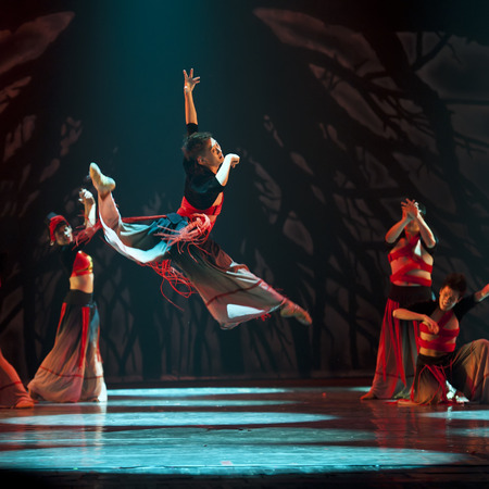 CHENGDU - OCT 18, 2011: Chinese Yi national dancers perform contemporary dance on stage at JINCHENG theater.