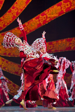 CHENGDU - OCT 17: Chinese Yi national dancers perform folk dance on stage at JINCHENG theater. Editorial