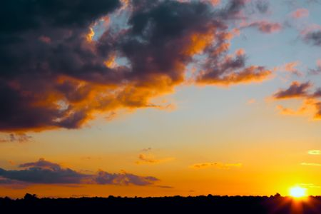 Sunset. Sun at the time of the event horizon. The tragic cloudscape photo