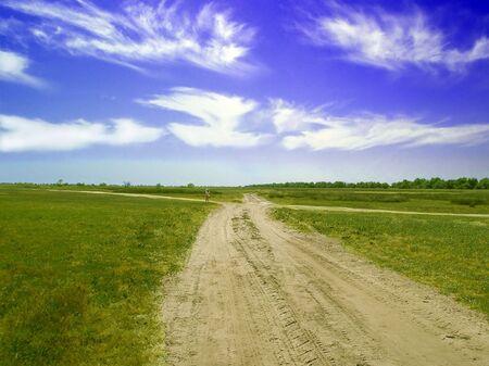 Rural sandy road.The little girl away on rural sandy road among grassland