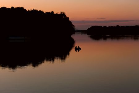 Fishermen on a boat floating on the lake after sunset in the quiet autumn weather photo