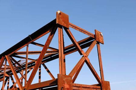 Fragment of rusty metal pillar against background of blue sky