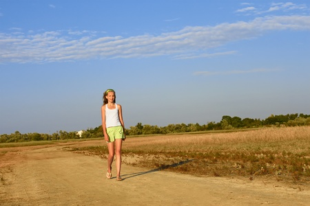 Teenage girl walking on the sandy village road. Summer heat. Kinburn Spit near Ochakiv, Ukraine