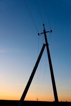 A pillar of electric transmission lines against the blue sky after sunset photo