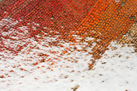 A fragment of an old colored mosaics partially covered with snow. Beginning of winter
