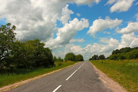 Rural paved road among the forest and meadows  Stock Photo