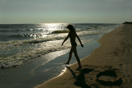 Teenage girl on an empty sea beach. Silhouette
