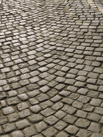 Part of urban square covered with cobblestone. Sunlight reflected on the stones Stock Photo