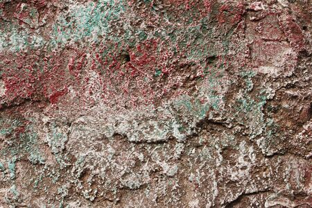 The surface relief of concrete partially covered with colored paints photo