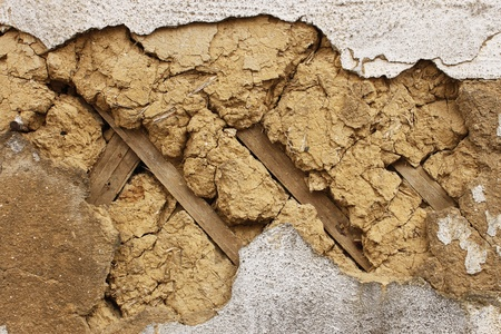fissures: A fragment of an old dilapidated mud walls. Wooden slats are used as fitting