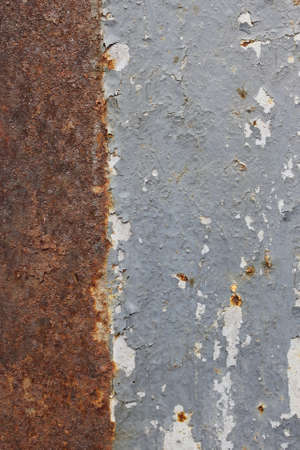 Rusty metal surface is covered with paint layers. Vertical photo