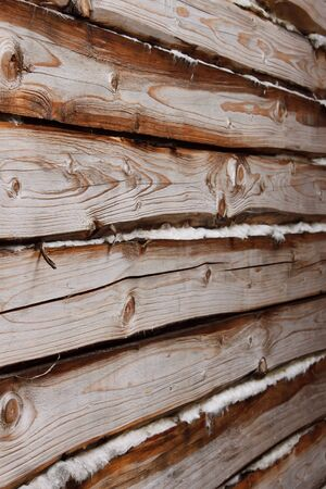 Detail of a wall of parallel wooden logs with insulation between them photo